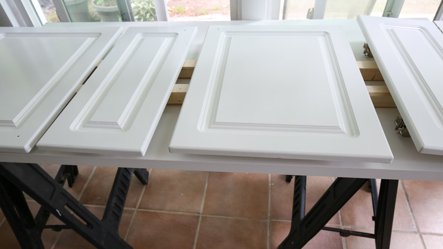 setup for painting cabinets using sawhorses and wood