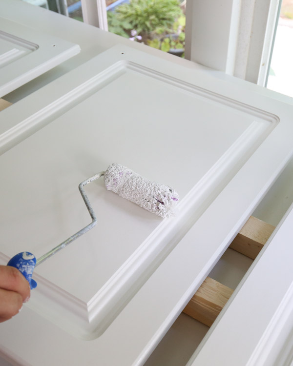 priming kitchen cabinets with a paint roller