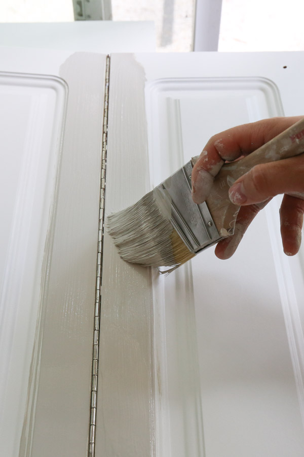 painting kitchen cabinets with a paint brush to cut in