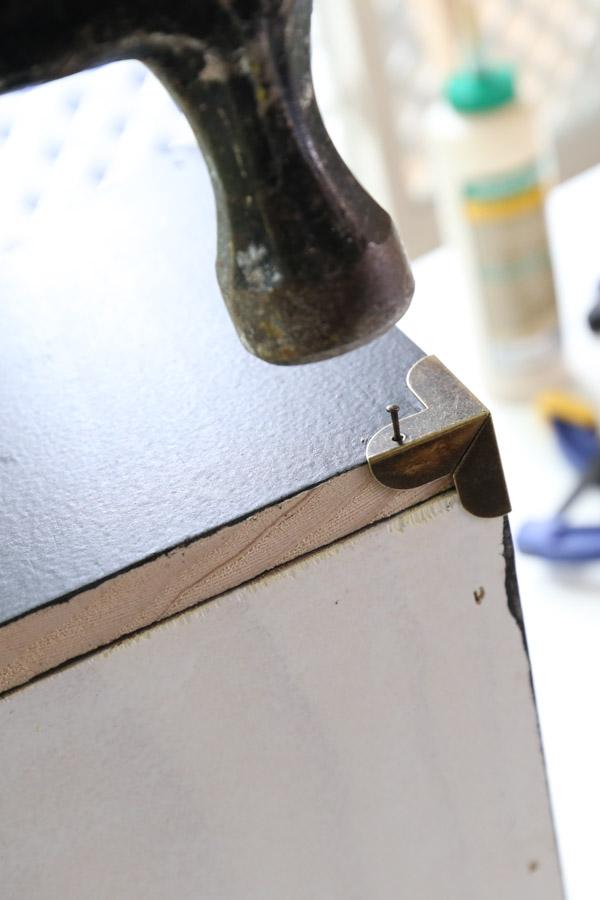 adding brass corner brackets to desk organizer with a hammer and nails