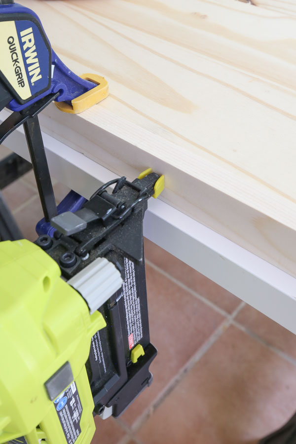 Attach the 1x2 boards along the sides of the plywood panel with brad nailer and wood glue
