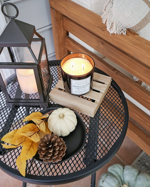 fall decor on side table with mini white pumpkin, fall candles, leaf stem, and pinecone