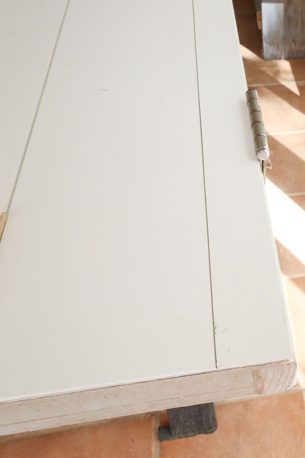 shiplap board cut to size for remaining space between boards and door hinges