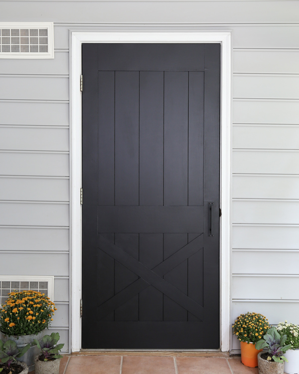 DIY faux barn door painted black on back porch