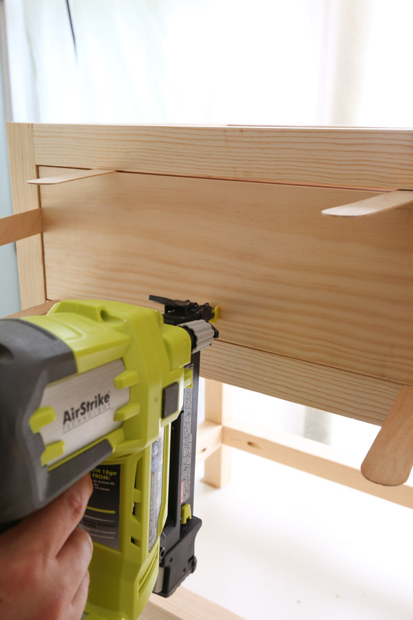 attach drawer face to nightstand with brad nailer and wood glue