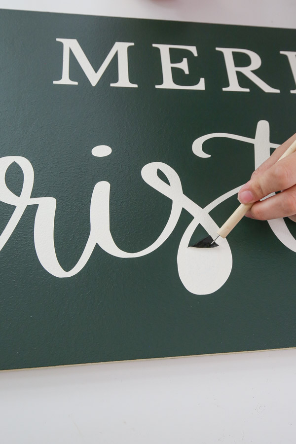 using a vinyl weeding tool to remove small parts of vinyl stencil from DIY sign