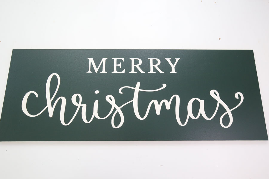 diy farmhouse christmas sign with green paint and white lettering before attaching frame
