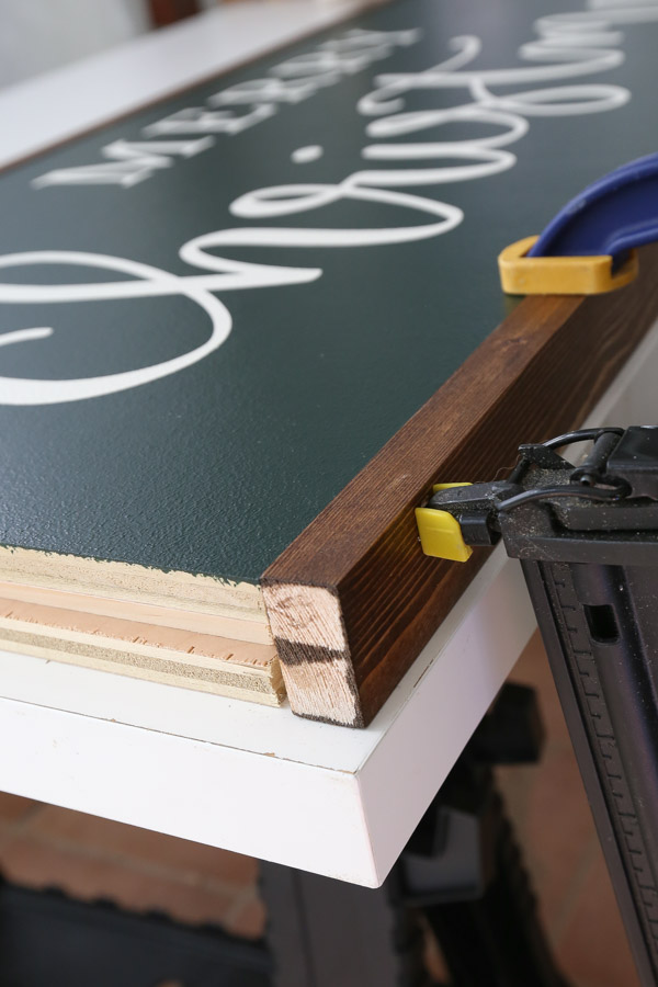 using a brad nailer to attach frame board to Christmas sign DIY