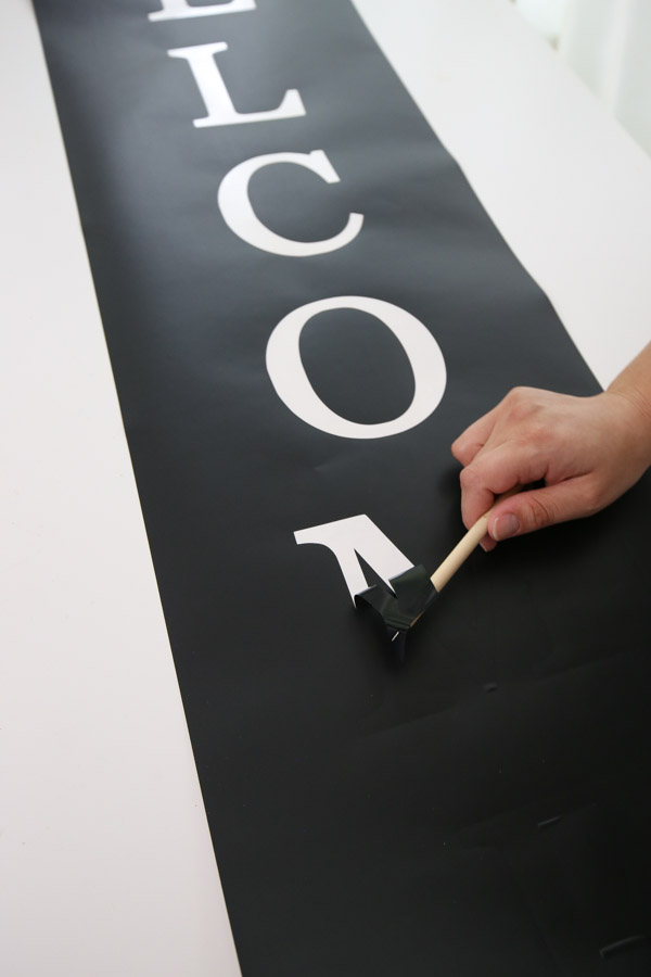 weed the vinyl stencil for the DIY welcome porch sign