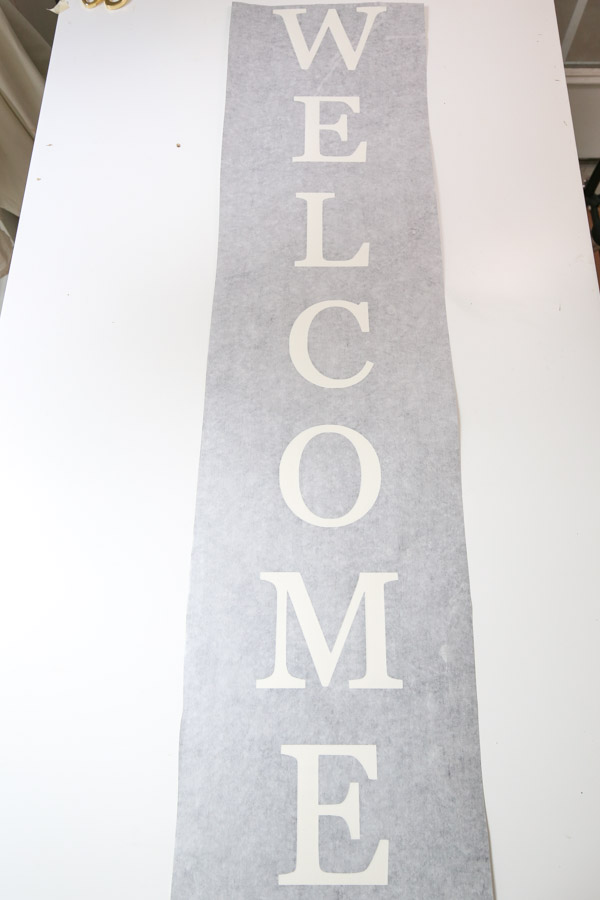 transfer tape applied to vinyl stencil for DIY welcome sign