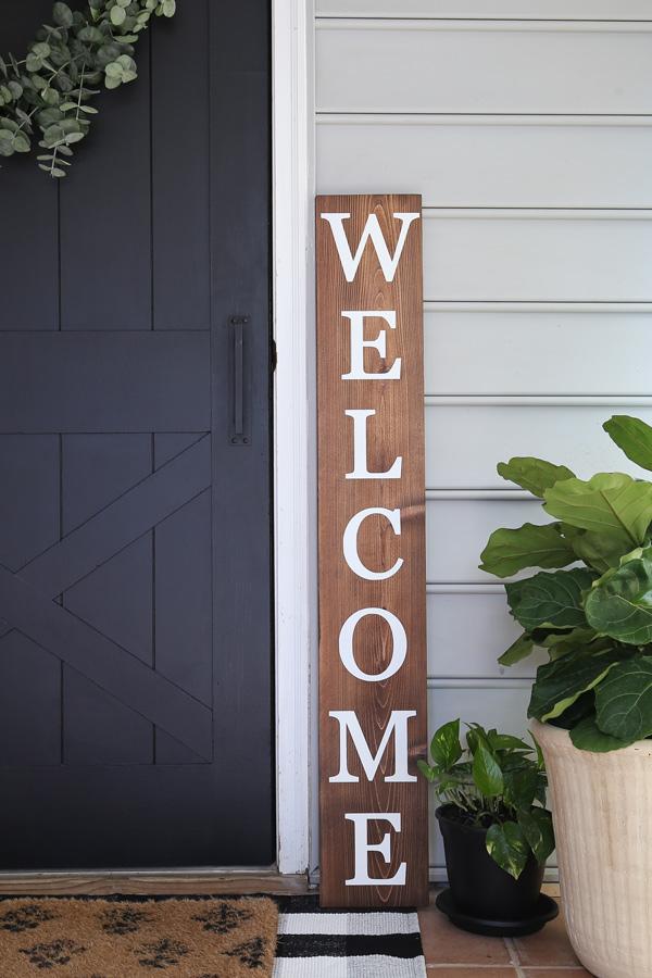 DIY welcome sign next to door and plants