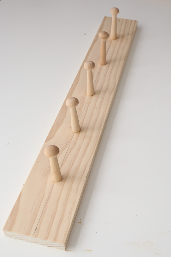 wooden shaker pegs in wood on DIY coat rack shelf