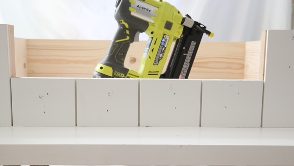 adding shiplap to front of DIY dog bed frame with wood glue and nailer