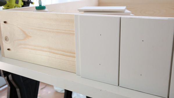 Attach shiplap boards to the sides and back of the dog bed frame