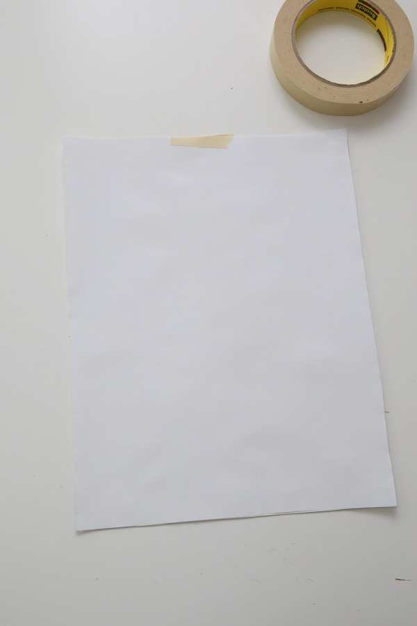 Tape the freezer paper on top of the letter size paper with a small piece of masking tape