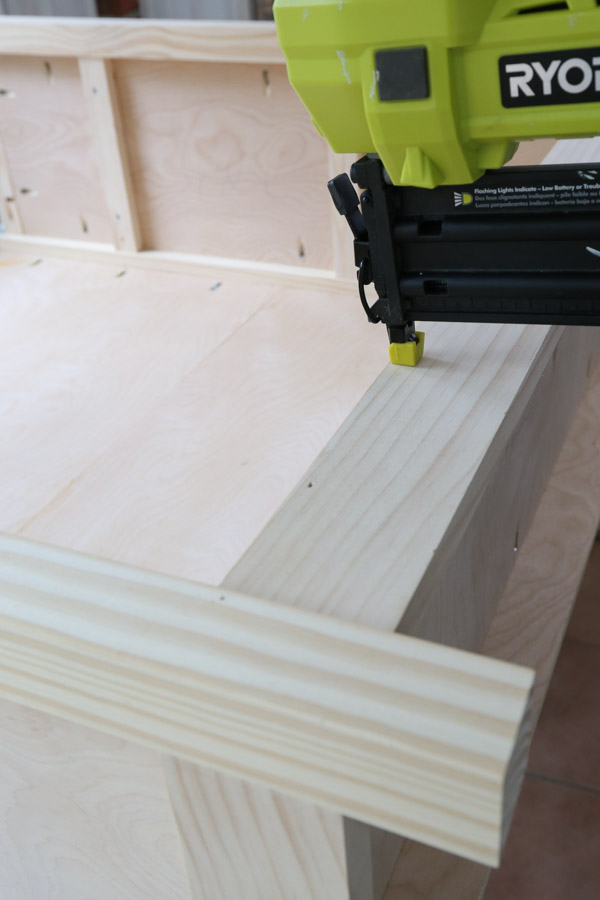attach 1x3 trim to bottom shelf front with brad nailer to DIY bookcase