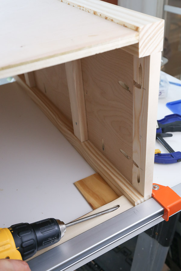 attach 1x2 trim to top shelf front with drill and kreg screws