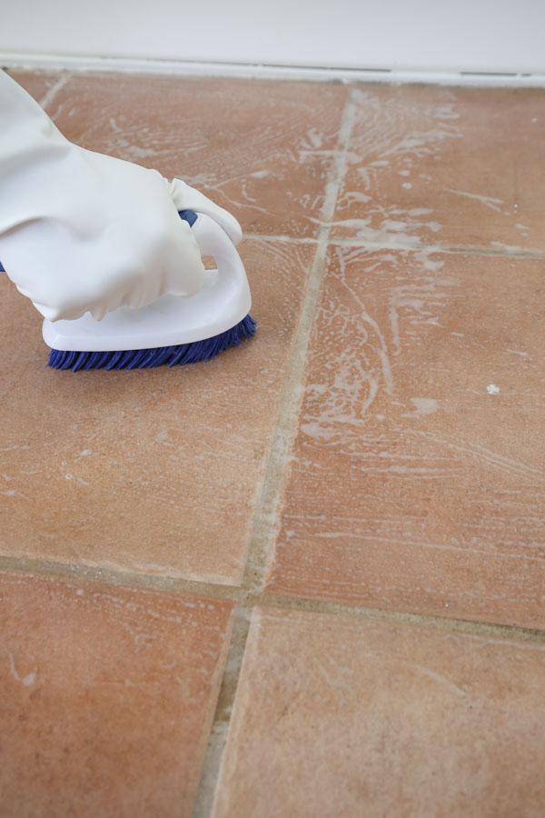 scrubbing old tile floor with cleaner