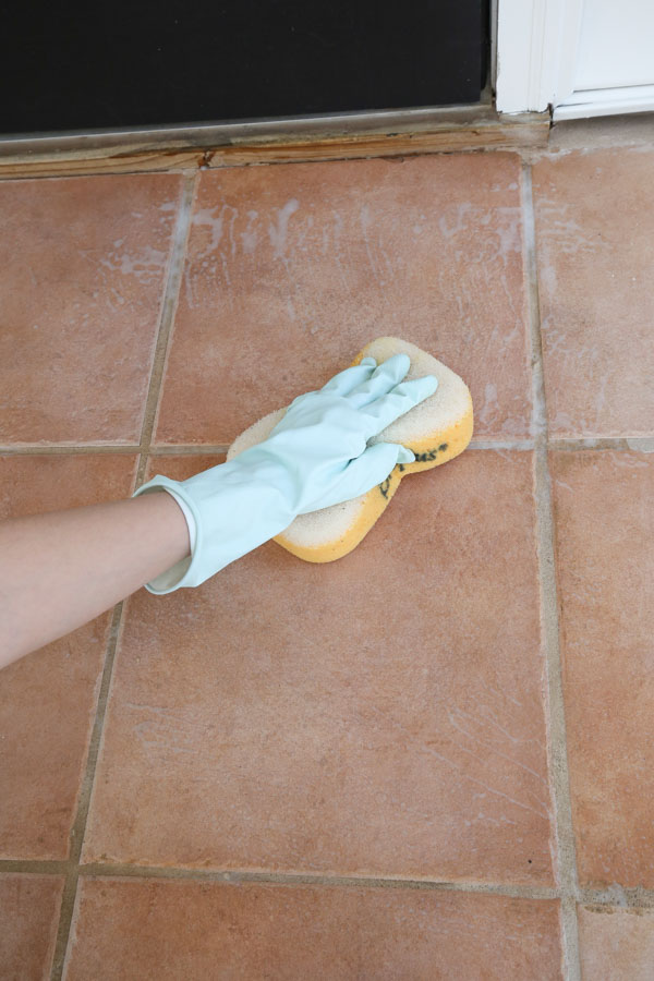 wiping old tile floor with water and sponge