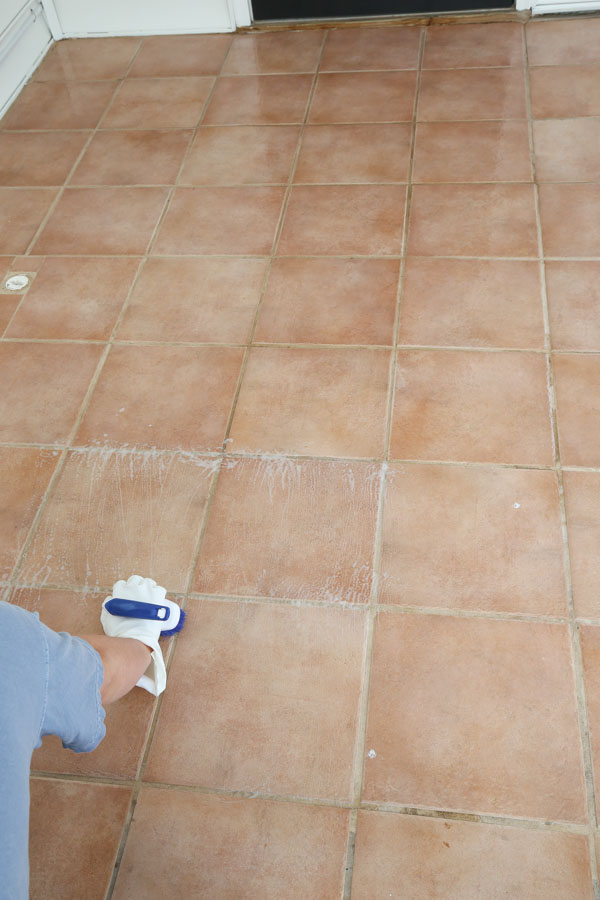 working in sections, scrubbing old tile floor with cleaner
