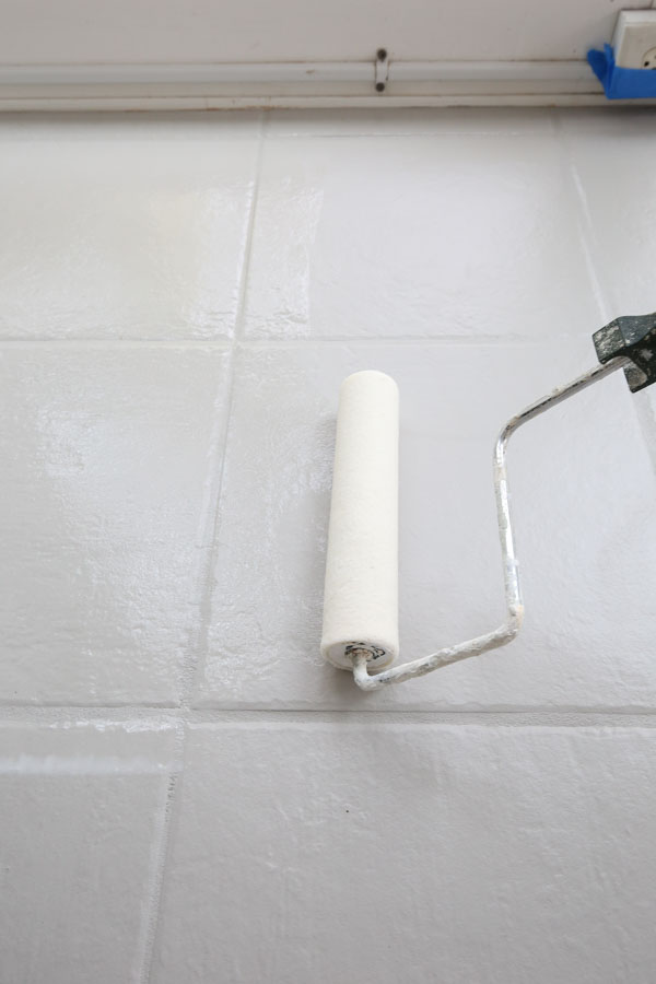 using a roller to apply the top coat over painted tile floor