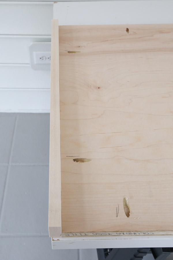 attach 1x2 trim to workbench top with wood glue and kreg screws