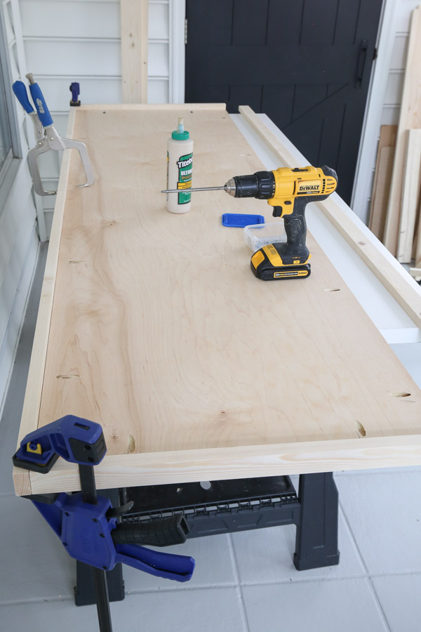 attach 1x2 trim to workbench top with wood glue and kreg screws and clamps