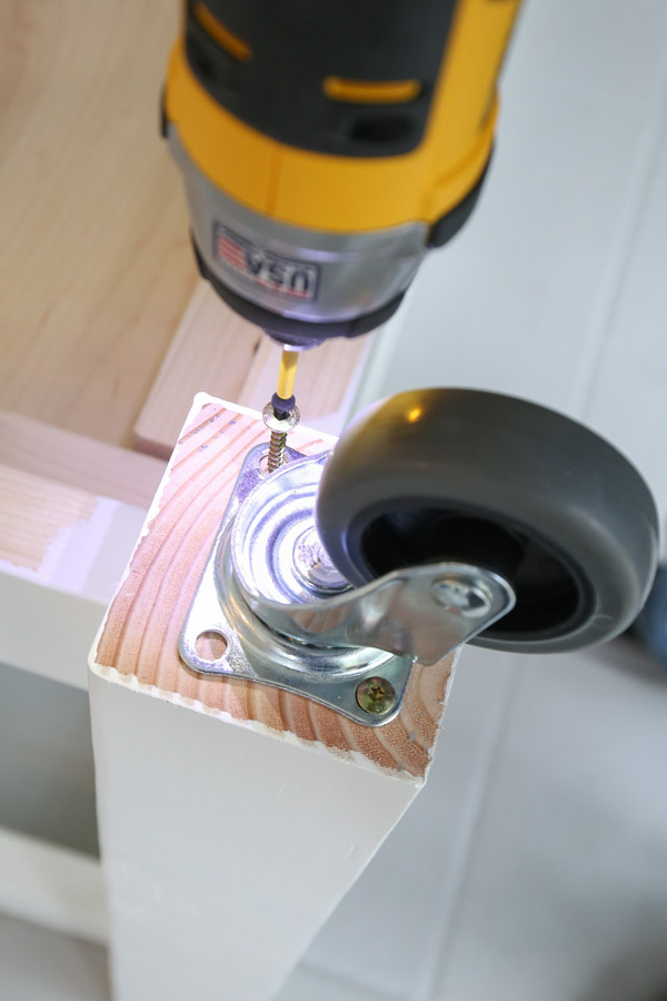 attach caster wheels with screws to DIY mobile workbench