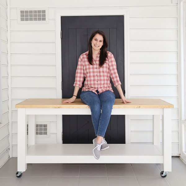 woman woodworker sitting on DIY workbench