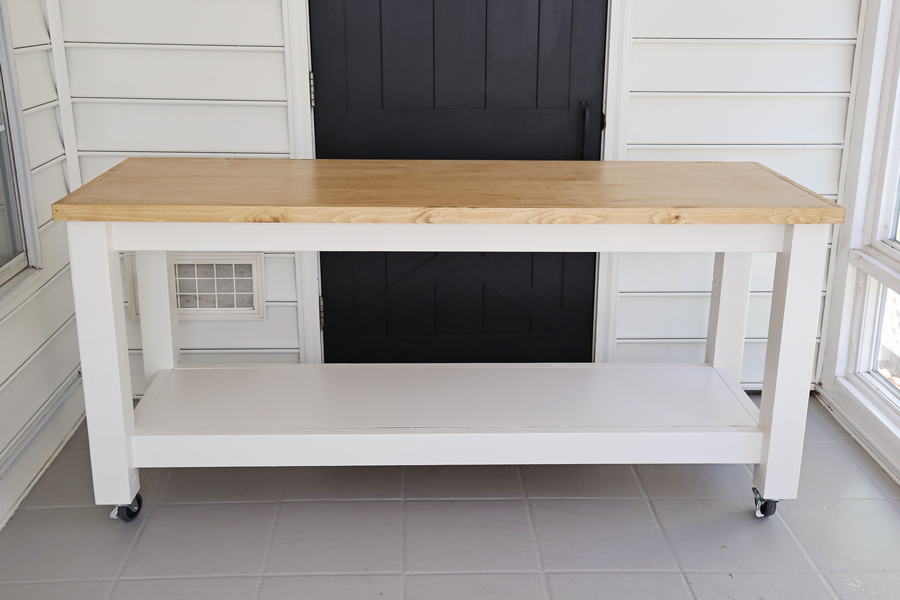 DIY rolling workbench with painted white frame and stained top