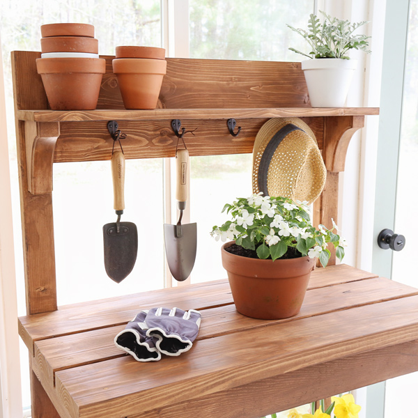 up close of rustic DIY potting bench with pots, flowers, shovels, and hat