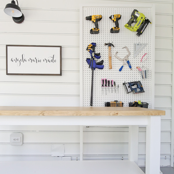small workshop with DIY workbench and tool pegboard wall