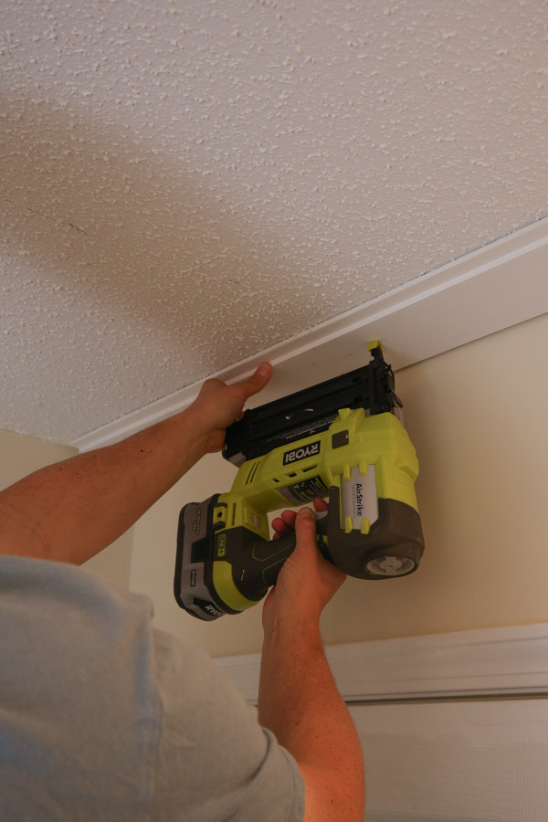 installing first shiplap board to ceiling with brad nailer