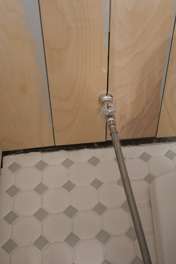 vertical shiplap bathroom installation and cutting around pipes