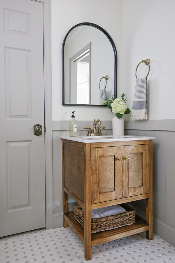 DIY bathroom makeover reveal with vertical shiplap, grey trim, wood bathroom vanity, and black arch mirror