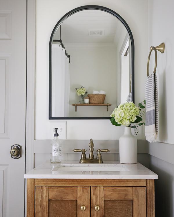 black arched mirror over wood bathroom vanity