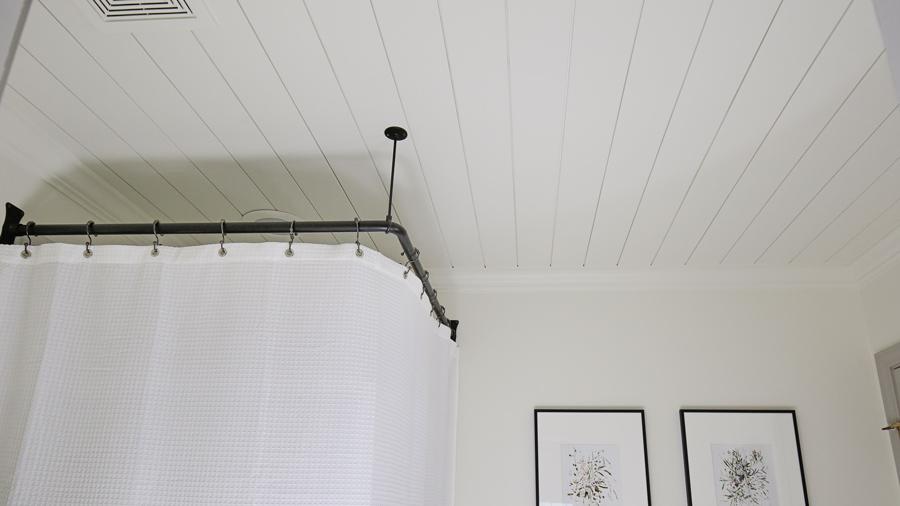 DIY shiplap ceiling in a bathroom with corner shower rod