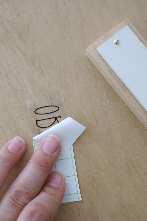 peeling backing paper off of vinyl plant labels