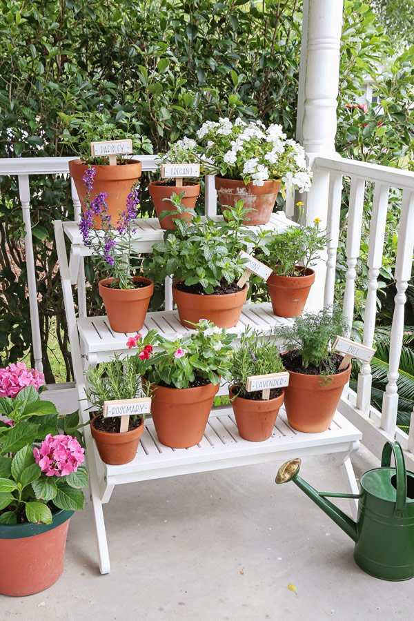 tiered plant stand painted for a makeover with plants, flowers, and herbs