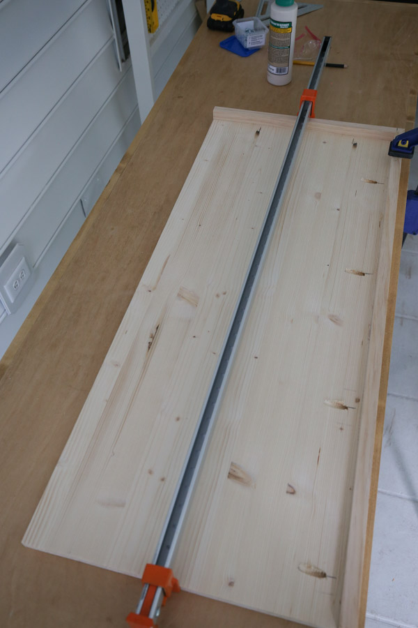 adding 1x2 trim to bench top with wood glue and pocket holes and clamps