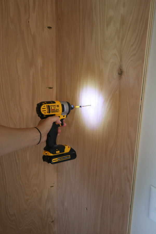 attaching built in cabinet to wall with drill and screws through wall stud