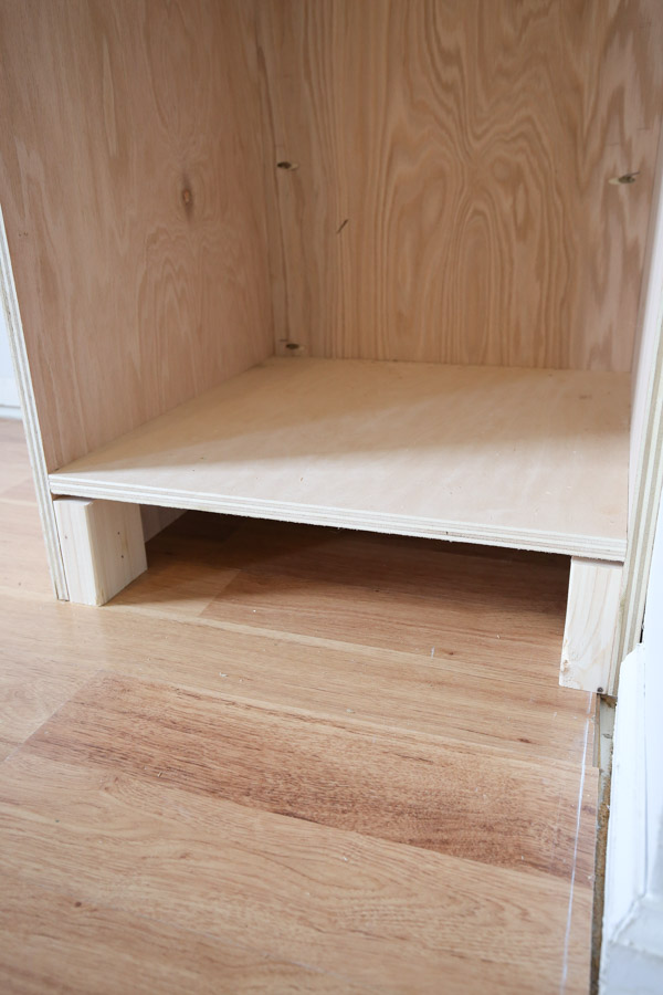 adding 2x4 wood blocks to cabinet frame bottom for trim