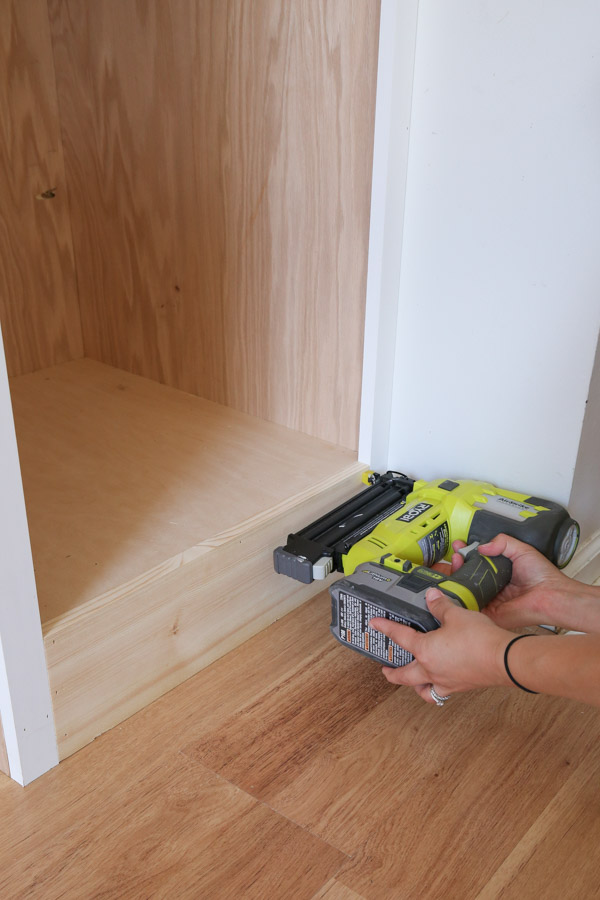 attaching bottom 1x6 trim to built in cabinet with brad nailer