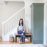 DIYer sitting on DIY built in bench in entryway makeover