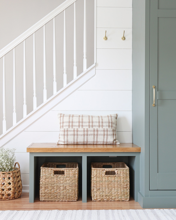 diy entryway bench built in with plaid pillow and brass wall hooks and DIY shiplap wall