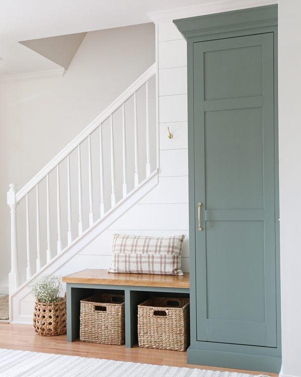 Stair railing painted white, sherwin williams retreat cabinet, and wood stained top on entryway bench