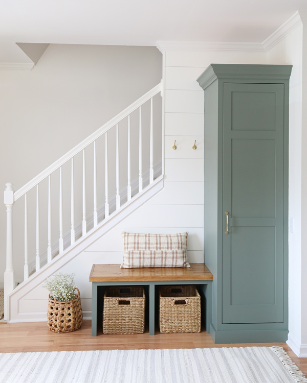 DIy entryway makeover with green painted built ins, DIy shiplap, and white painted stair railing