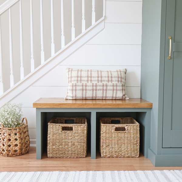 diy entryway bench with two seagrass baskets and DIY shiplap on angled wall