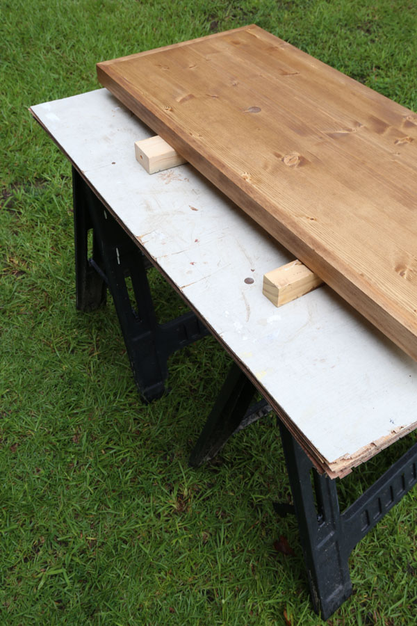 work space set up for applying polyurethane using sawhorses, plywood, and 2x wood under project