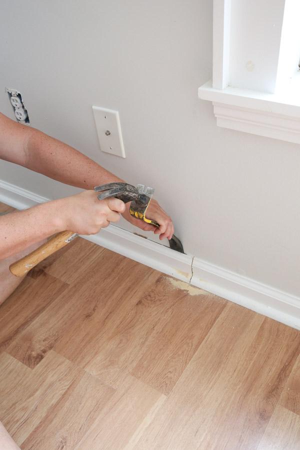 using prybar and hammer to remove baseboard